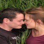 794582_young_couple_kissing_in_the_gras