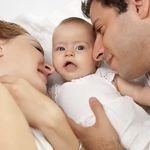 Loving parents with their cute little girl on bed