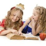 Two beautiful little princesses reading a magic book