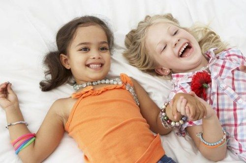 Two Young Girls Dressing Up Together In Bedroom